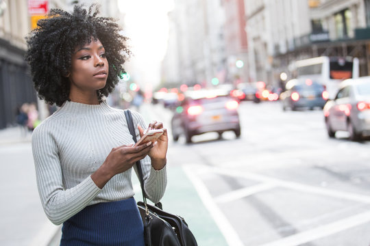 Woman with mobile device waiting for rideshare car service