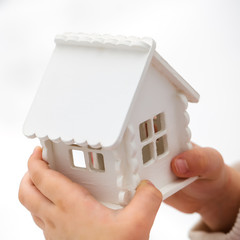 Child's hands is holding a toy house on a white background
