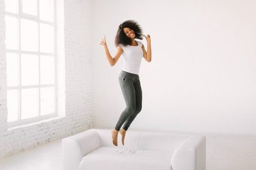 An African American young woman jumping on white bed