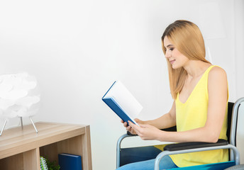 Young woman in wheelchair reading book indoors