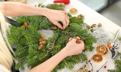 Female florist making Christmas wreath  in flower shop