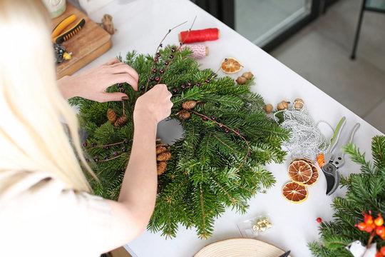 Female florist making Christmas wreath  in flower shop