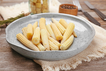Plate with fresh young baby corn on wooden table, closeup