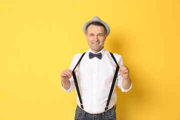 Portrait of stylish male pensioner on color background