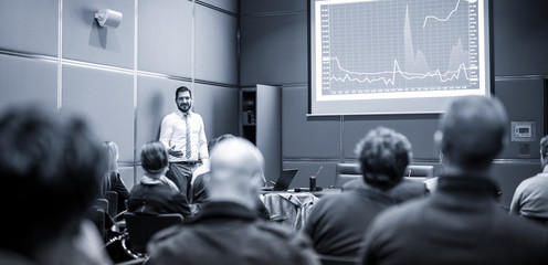 Public Speaker Giving a Talk at Business Meeting. Audience in the conference hall. Business and Entrepreneurship concept. Blue toned black and white image.