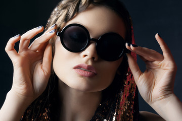 Close up studio portrait of young beautiful sexy woman wearing stylish black round sunglasses, posing on dark background. Fashion, beauty, night party, advertising concept.