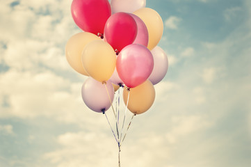 Big bunch of pastel colour balloons floating with calm sky toned vintage