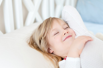 Little cute girl wake up in bed.  Child stretching arms. Smiling and satisfied  after healthy sleep. Happy careless childhood concept. Good morning concept