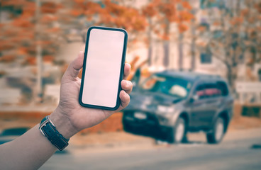 man hand holding smartphone with car crash accident background