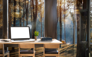 Mock up of wooden desk, laptop with white blank scrreen ,smartphone  and boooks in modern house with pine forest background outside
