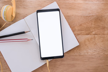 smartphone with blank screen on blank notebook  on wood table