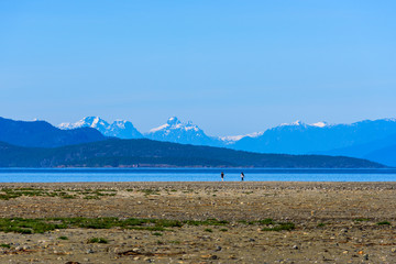 Rathtrevor Beach with view of Snowcapped Mountain Ranges at low tide in Parksville, British Columbia, Canada