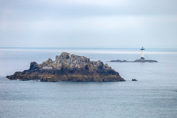 Scenic view of a lighthouse a small island on the coast of Normandy France Europe