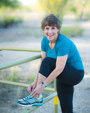 Active Woman Smiling Tying Shoes Outside on Jogging Trail