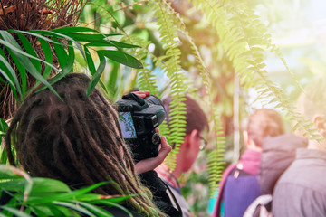 Concept - photography on an excursion. Photographer with dreadlocks on his head examines on screen camera picture taken.