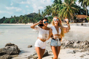 Two cute beautiful girls in Boho style dressed shirts shorts light cape bracelets necklaces, in the hair decorative feathers colored, go embracing the beach against the sea and the rocks
