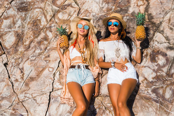 Two cute beautiful girls in Boho style dressed shirts shorts light cape bracelets necklaces, in the hair decorative feathers colored, straw hats, with pineapple in their hands on  background of cliffs
