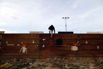 A man looks on near prototypes of U.S. President Donald Trump's border wall with Mexico behind the current border fence, in this picture taken from the Mexican side of the border in Tijuana