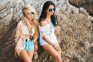 Two cute beautiful girls in Boho style dressed shirts shorts light cape bracelets necklaces, in the hair decorative feathers are colored, on the background of the sea and the rocks
