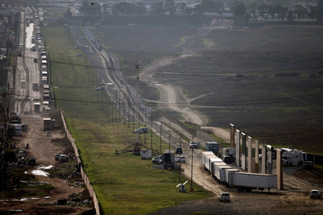 Prototypes for U.S. President Donald Trump's border wall with Mexico are shown blocked by trucks before Trump's visit to the area in this picture taken from the Mexican side of the border, in Tijuana