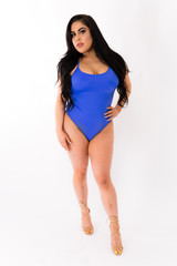 Young plus size hispanic woman in blue one piece and high heels posing on a white background