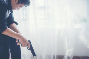 business gangster saying a prayer with his gun