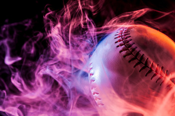 Close up of a white baseball ball in multi-colored red smoke from a vape on a black isolated background