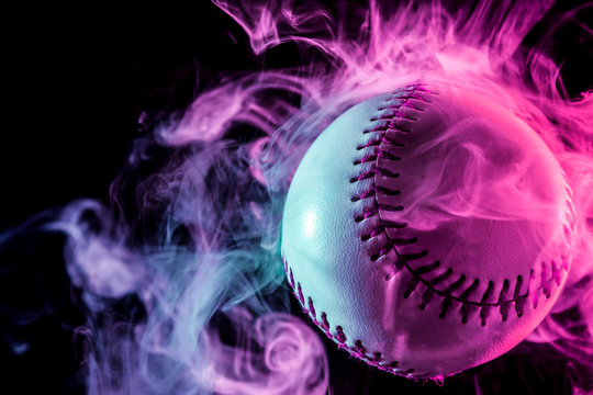 White baseball ball in multi-colored red smoke from a vape on a black isolated background