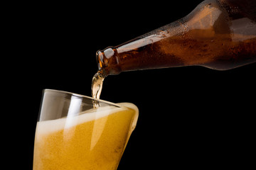 Papiers peints Biere, Cidre Pouring beer into mug or glass isolated on black background object alcohol celebration concept