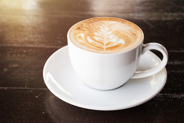 Cup of coffee with latte art on wooden table background