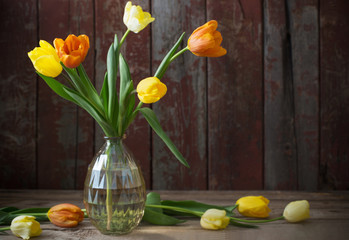 tulips in glass vase on old wooden background