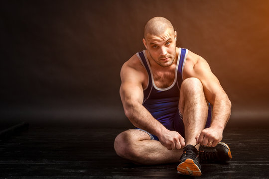 A young athletic man in blue wrestling tricky and blue shorts ties up shoelaces on sneakers on a black isolated background in a photo studio