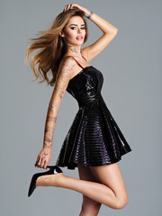 Beautiful trendy woman in black dress with a tattoo on the hand.