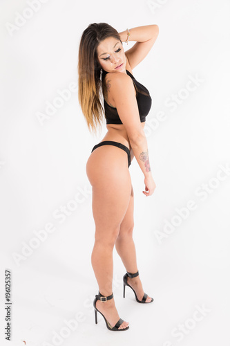 85a98a72c Young fit hispanic woman in black two piece and black high heels posing on  a white background