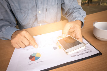 Business man analyzing investment charts with smart phone and calculator on office desk table.Close up.Financial Report Revenue Statistical Accounting Concept.