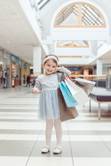 Portrait of cute adorable smiling Caucasian preschool girl going shopping in mall. Happy kid holding shopping bags.