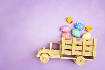 Wooden toy truck with Easter eggs and chickens in the back on purple background. Space for text.