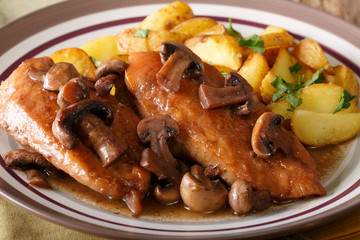 Chicken Marsala with garnish of potatoes macro. horizontal