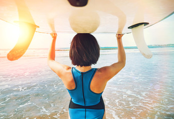 Woman takes surfboard on head and goes in ocean waves