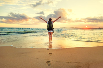 Woman backpacker stay on ocean surf line at sunset time