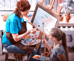 Artist painting easel in studio. Authentic grandmother and kids girl paints with palette watercolor paints palette and brush morning sunlight. Courses on drawing for children and adults.