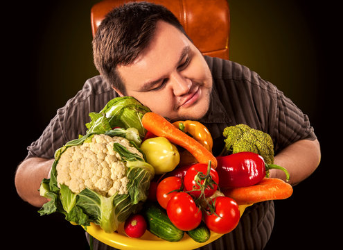 Diet fat man eating healthy food with vegetables cauliflower and sweet pepper with radish, tomatoes for overweight male. Male trying to lose weight first time. Dietary breakfast.