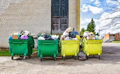 Green and yellow containers with garbage near the house