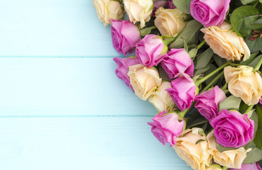 Beautiful roses on a turquoise (blue) background. Roses and pearls on a wooden background