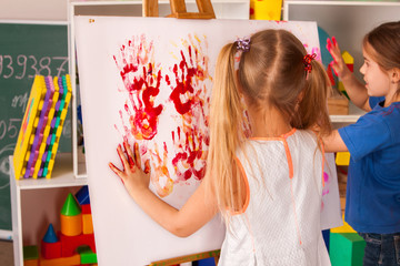 Children painting finger on easel. Group of kids girl and boy with teacher learn paint in class school. Child picture on background. Unusual ways of drawing.