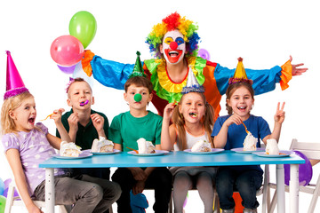 Birthday child clown playing with children who eat cake. Kid with nose bunny fingers prank. Fun of group people pose for camera sit at table white background. Mom arranged holiday for her daughter.