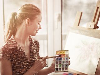 Artist painting on easel and palette in studio. Authentic girl paints with oil brush in morning sunlight dawn light toning window background. Sale of artistic goods. How to mix paint lesson.
