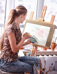 Artist painting on easel and palette in studio. Authentic girl paints with oil brush in morning sunlight dawn light toning . Private business in drawing for student. How to draw watercolor.