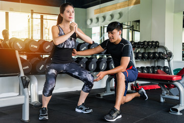 Woman doing squat with a personal trainer
