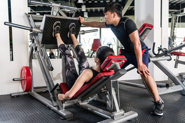 Woman using weights press machine for legs